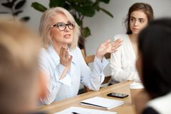 Aged businesswoman, teacher or business coach speaking to young. Attractive aged businesswoman, teacher or mentor coach speaking to young people, senior women in stock image