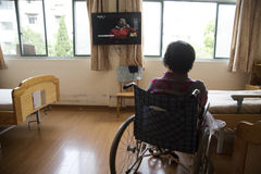 Woman in aged care home watching TV Royalty Free Stock Photo