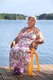 Aged Caucasian woman sitting in chair on lake jetty Royalty Free Stock Photography
