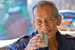 An aged cheerful old man holding a cup of coffee Royalty Free Stock Images
