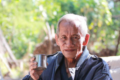 An aged cheerful old man holding a cup of coffee Stock Image