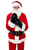 Aged cheerful Santa wearing boxing gloves Stock Images