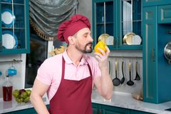 Aged Chef in apron and bonnet sniffing yellow paprika. With closing eyes. Cook loves paprika holding in his hand. Tough guy sniffs pepper at kitchen. Guy sniff Royalty Free Stock Photos