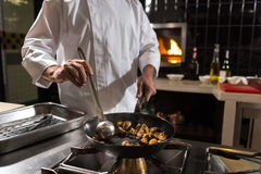 Aged chef frying mushrooms in the kitchen of the restaurant Royalty Free Stock Image