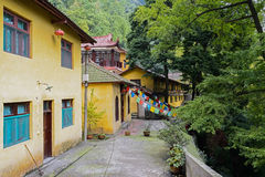Aged Chinese buildins with yellow surface in woody mountain Stock Photo