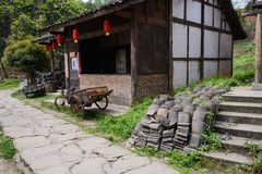 Aged Chinese dwelling house. A shabby aged dwelling house in Chinese traditional style by the stone paved footway Royalty Free Stock Photo