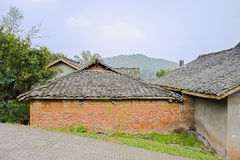 Aged Chinese farmhouses by slopy countryroad in sunny spring Stock Images