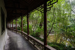 Aged Chinese gallery by pond in summer woods Royalty Free Stock Photos