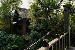 Aged Chinese traditional buildings in woods near wooden bridge. Aged Chinese traditional buildings in woods near a wooden bridge,Huanglongxi town,Chengdu,China Royalty Free Stock Photo