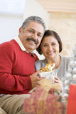 aged christmas couple holding middle present Στοκ Φωτογραφίες