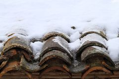 Aged clay roof tiles snowed under winter snow Stock Image