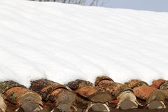 Aged clay roof tiles snowed under winter snow Stock Photos