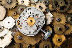 Aged clock mechanism close-up. Retro hand watches parts on bronze gears background Royalty Free Stock Images