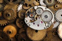 Aged clock mechanism macro view. Retro hand watches parts on bronze gears background Stock Image
