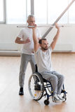Aged coach teaching and helping the invalid in the gym. The process of rehabilitation. Concentrated muscular aged coach helping the disabled patient and Royalty Free Stock Image