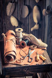 Aged cobbler workplace with shoes, laces and tools. On old wooden table royalty free stock images