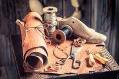 Aged cobbler workplace with tools, shoes and laces Royalty Free Stock Image