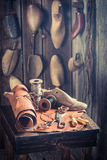 Aged cobbler workplace with tools, shoes and leather Royalty Free Stock Photo