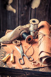 Aged cobbler workshop with tools, leather and shoes. On old wooden table Royalty Free Stock Photography