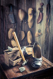 Aged cobbler workshop with tools, shoes and laces Royalty Free Stock Images