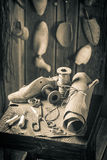 Aged cobbler workshop with tools, shoes and leather royalty free stock photo