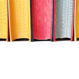Aged colorful book spines on white. Aged colorful book spines. Close up, texture, hard cover. White background. Copy space Royalty Free Stock Photo