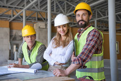 Aged constructors and contractor looking at camera during work on construction site Royalty Free Stock Image