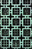 Aged Copper - French Fleur de Lis Pattern. Green tinted copper texture in a french inspired pattern, squares, checkers and fleur de lis stand out on the black Royalty Free Stock Image