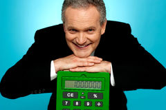 Aged corporate male resting face on big calculator Royalty Free Stock Images