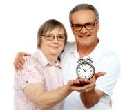 Aged couple with alarm clock on plam Stock Images