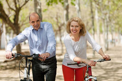 Aged couple with bicycles staying in park Royalty Free Stock Image