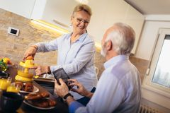 Senior couple busy look at digital tablet while having delicious breakfast at home kitchen royalty free stock images