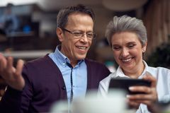 Aged couple discussing smth in mobile phone. Enjoyable meetings. Waist up portrait of happy excited aged men discussing something interesting at mobile phone royalty free stock photos