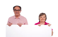 Aged couple displaying blank billboard Royalty Free Stock Photography