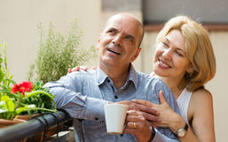 Aged couple drink tea on balcony Stock Photo