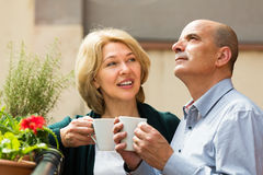 Aged couple drink tea on balcony Stock Images