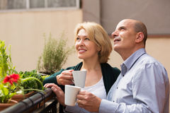 Aged couple drink tea on balcony Royalty Free Stock Image
