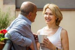 Aged couple drink tea on balcony Royalty Free Stock Photography