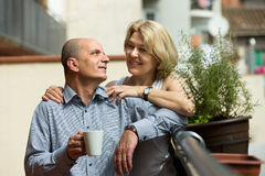 Aged couple drink tea on balcony Royalty Free Stock Photography
