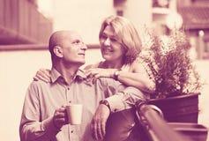 Aged couple drink tea on balcony Stock Photos