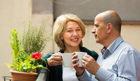 Aged couple drink tea on balcony Royalty Free Stock Images