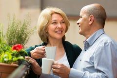 Aged couple drink tea on balcony Royalty Free Stock Photo
