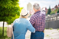 Aged couple enjoying each other. Golden lovers. Backs of pensioners married couple while travelling together, men pointing at something royalty free stock image