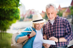Aged couple enjoying each other. Green at heart. Delighted and concentrated aged couple in town looking at a map while travelling together and having nice time Royalty Free Stock Photo