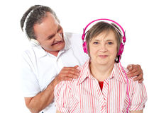 Aged couple enjoying music over white background Royalty Free Stock Photography