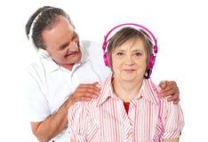 Aged couple enjoying music over white background Royalty Free Stock Photography