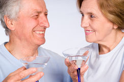 Aged couple with glass Stock Image