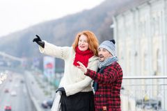 Aged couple happy standing on bridge. Woman and man point to other side. Couple of tourists showing interests. Surprised guy and w royalty free stock photo