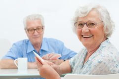 Aged couple leisure. Happy smiling senior couple playing cards together at home Royalty Free Stock Photo