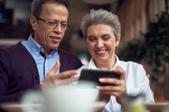 Aged couple look with interest in mobile phone. Enjoyable meetings. Waist up portrait of happy smiling aged men discussing something interesting at mobile phone stock images